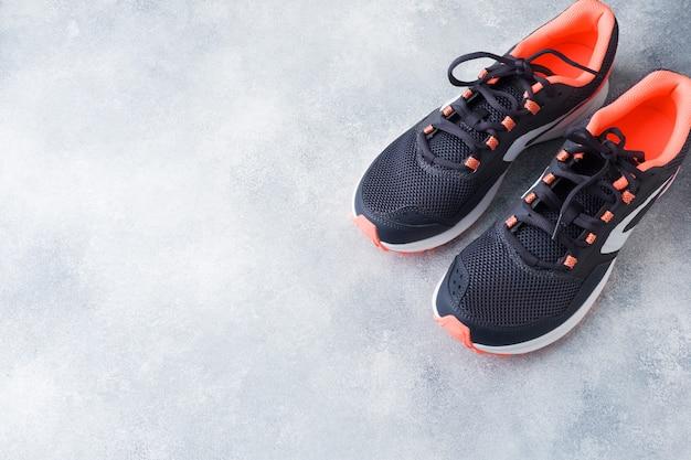 Stile di vita sano, sneaker sportive su superficie grigia