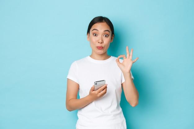 Stile di vita, tecnologia e concetto di e-commerce. bella cliente femminile asiatica soddisfatta, cliente del negozio online, lascia un feedback positivo, tiene in mano lo smartphone e mostra il gesto giusto