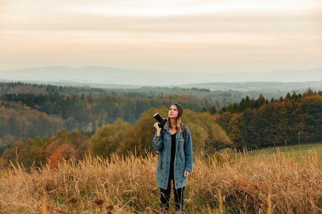 Stile donna con macchina fotografica e zaino in campagna con le montagne