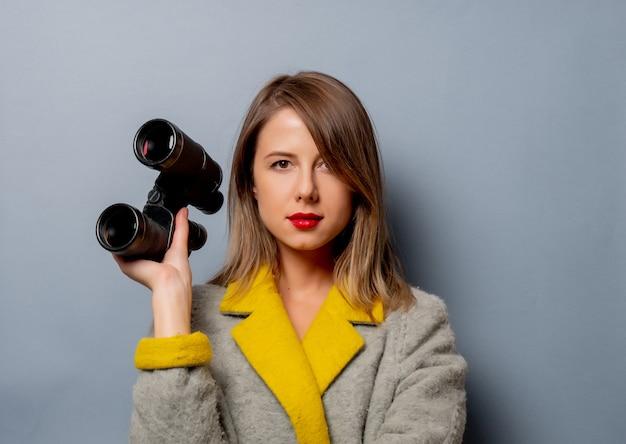 Stile donna in cappotto con il binocolo