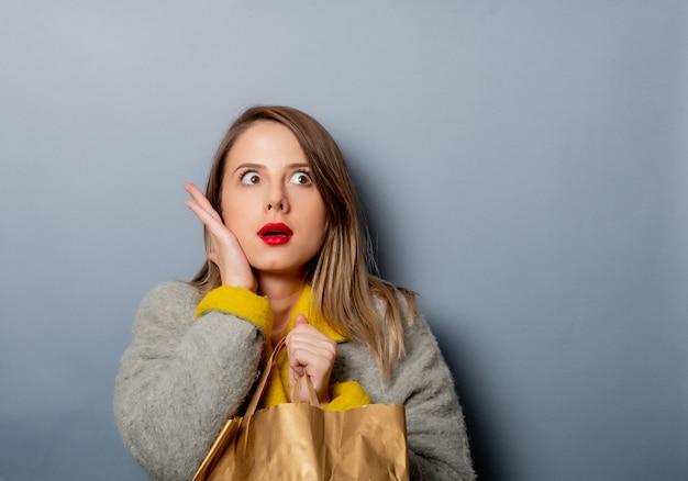 Stile donna in cappotto con la borsa della spesa