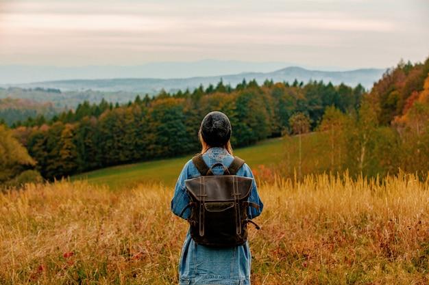 Stile donna in giacca di jeans e cappello con zaino in campagna con le montagne