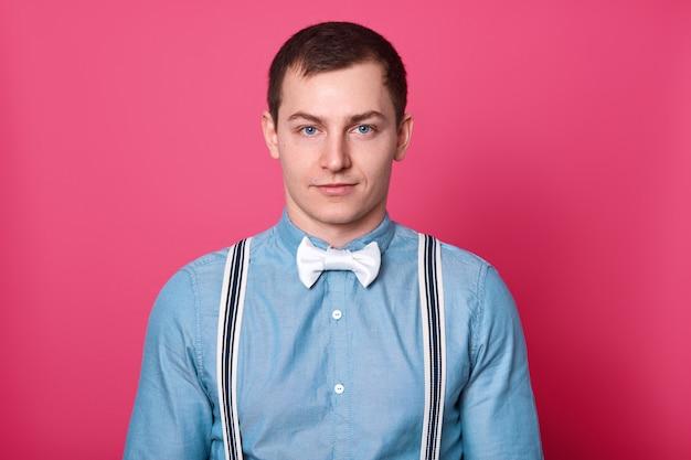 Stile e concetto di moda maschile. uomo dagli occhi blu bello con capelli scuri, pelle liscia, indossa camicia, papillon e bretelle, guarda, redy per data con la fidanzata, isolato sul muro rosa.