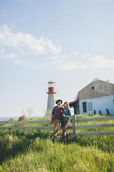 Stile indie di giovane coppia hipster innamorato a piedi in campagna, tenendosi per mano