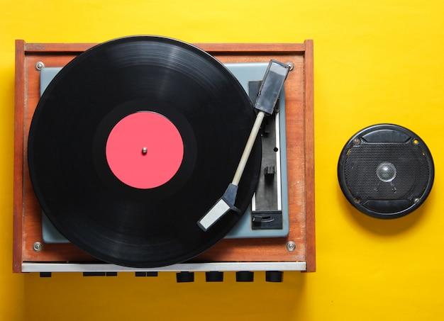 Stile retrò, attributi di cultura pop su uno sfondo giallo. lettore vinile, altoparlante.