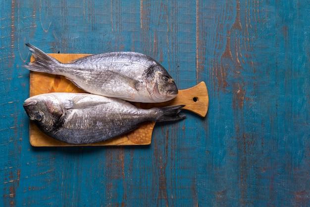 Stile rustico. cibo per i pesci. le aringhe pescano su un vecchio fondo di legno blu e copiano lo spazio per testo.