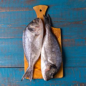 Stile rustico. cibo per i pesci. le aringhe pescano su una vecchia superficie di legno blu e copiano lo spazio per testo.