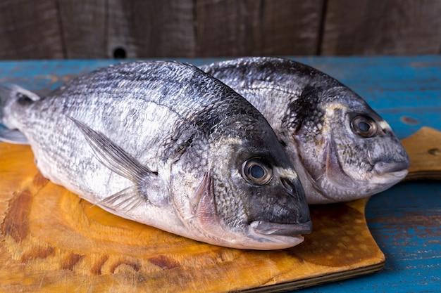 Stile rustico. cibo per i pesci. pesce aringhe su una vecchia superficie di legno blu