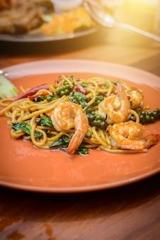 Stile tailandese dell'alimento dei frutti di mare piccanti in padella degli spaghetti in piatto arancio