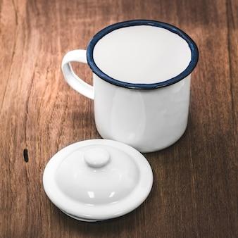 Stile vintage mug su fondo in legno. tazza da tè retrò realizzata in materiale di stagno.