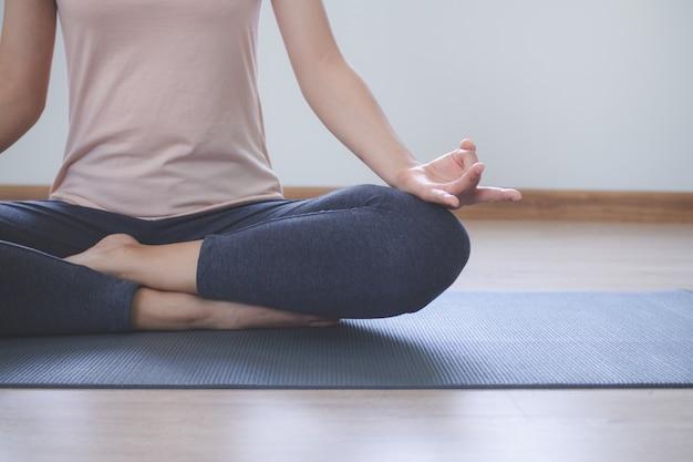 Stili di vita di yoga e meditazione. vista ravvicinata della giovane e bella donna praticare yoga namaste posa nel salotto di casa.