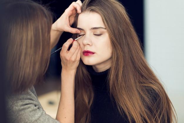Stilista anonimo che applica l'eyeliner sul modello