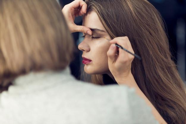 Stilista che applica ombretto scuro sul modello