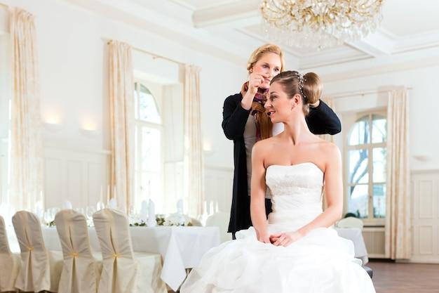 Stilista che blocca l'acconciatura di una sposa
