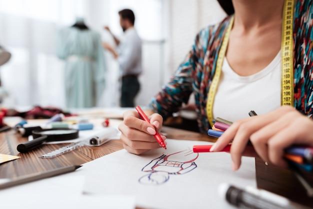 Stilista che disegna modello su carta.