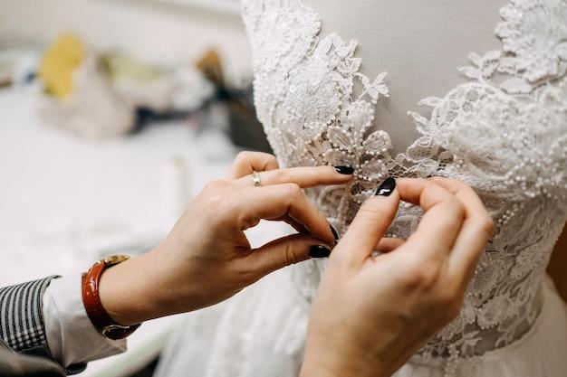 Stilista che lavora su un abito da sposa, appuntando il pizzo su un manichino