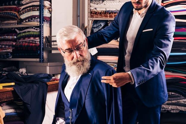 Stilista che prova cappotto blu sopra l'uomo anziano nel suo negozio