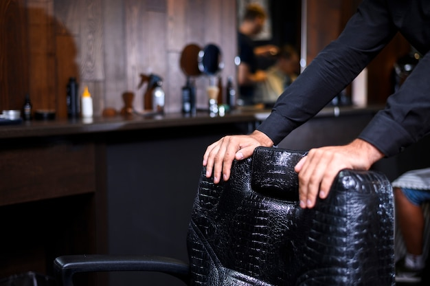 Stilista che si appoggia sulla sedia di cuoio del negozio di barbiere