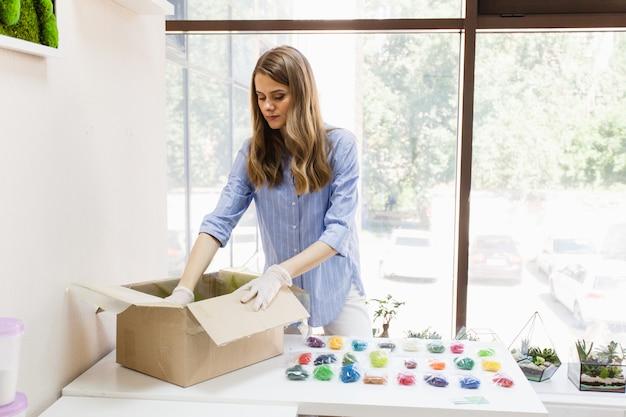 Stilista, decoratrice, fioraia che lavora con muschio, scatola con materiale, muschio, piante. fare affari, affari interni