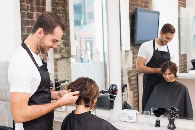 Stilista di capelli bello con il cliente al salone di capelli