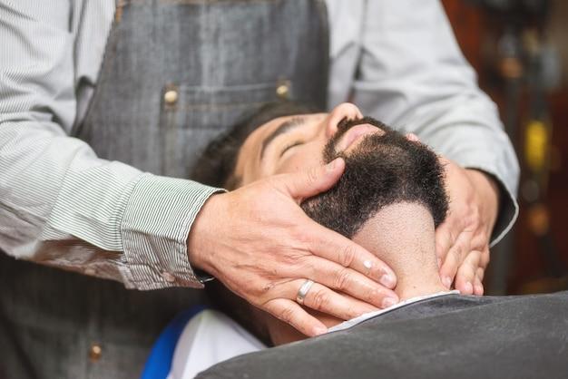 Stilista di capelli che applica dopo lozione della rasatura al negozio di barbiere.