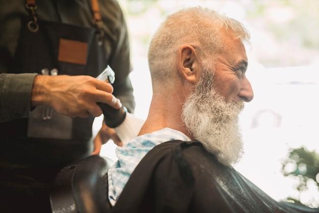 Stilista di capelli che corregge taglio di capelli nel salone