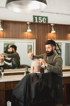 Stilista di capelli che fa taglio di capelli al cliente nel negozio di barbiere