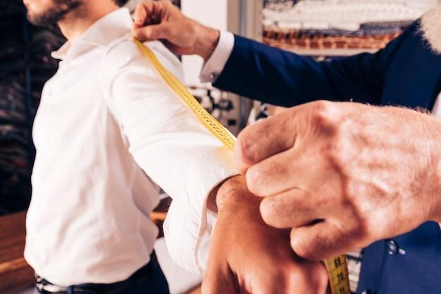 Stilista di moda maschile che misura le maniche in officina