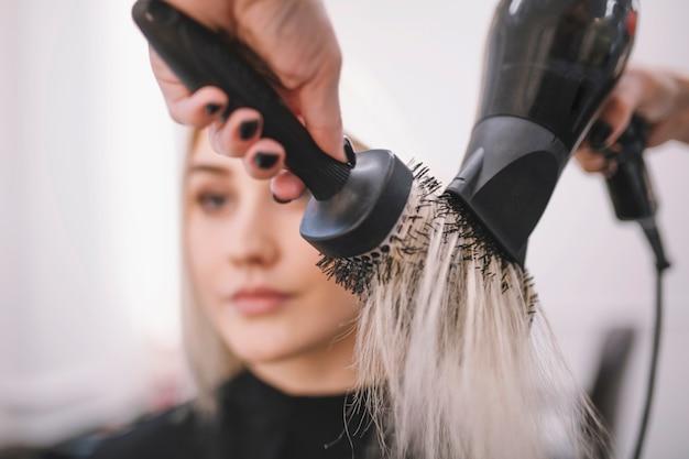Stilista di raccolto che asciuga capelli con la spazzola
