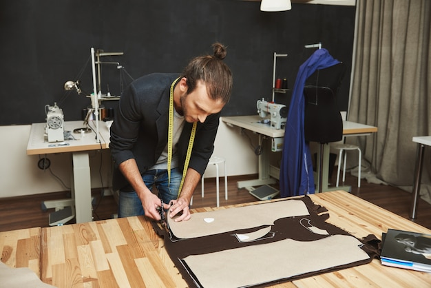Stilista maschio caucasico bello bello creativo maturo in vestito nero che taglia le parti dei vestiti da tessuto con le forbici, spendendo sera nello studio.