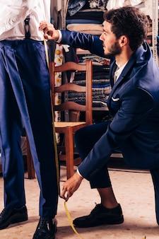 Stilista prendendo la misura dei pantaloni del cliente maschio nel negozio