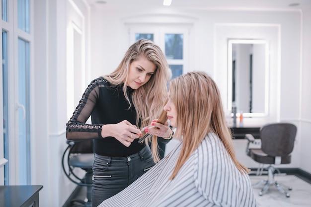 Stilista professionista che fa taglio di capelli nel salone