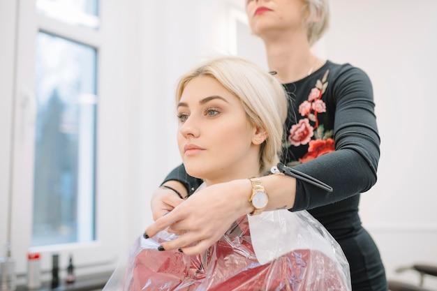 Stilista sicuro che prepara ragazza per taglio di capelli