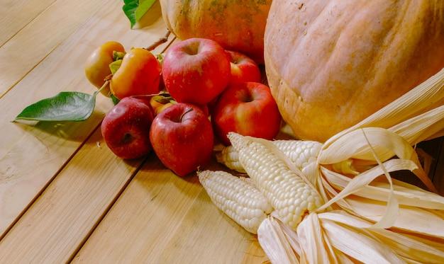 Still life con zucche persimmon mais e mele sul tavolo di legno