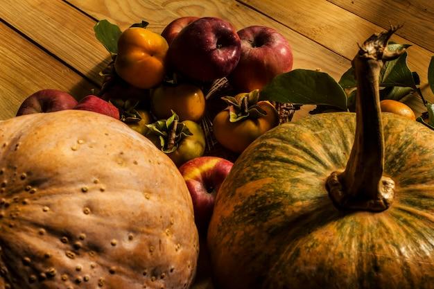 Still life con zucche persimmone mais e mele sul tavolo in legno sfondo nero