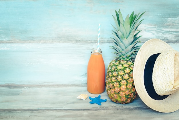 Stillife concetto estivo. ananas maturo, cappello di paglia e una bottiglia di succo multivitaminico di fronte a un legno rustico blu.