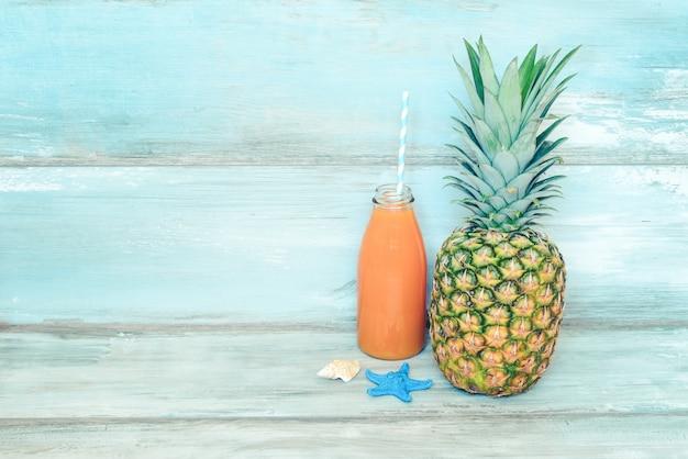 Stillife concetto estivo. un mucchio di frutta fresca, cappello di paglia e una bottiglia di succo multivitaminico di fronte a un legno rustico blu.
