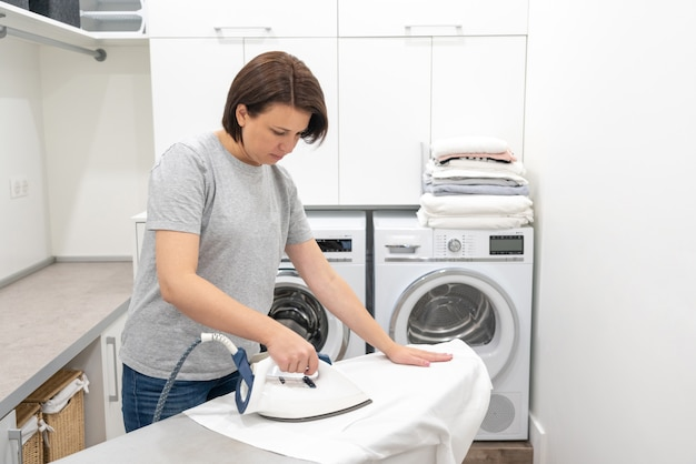 Stiratura della camicia bianca a bordo in lavanderia con lavatrice