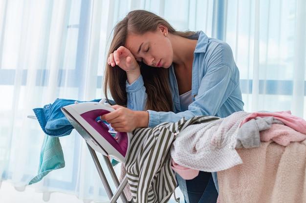 Stiratura donna sentirsi stanchi di stirare la pila di vestiti