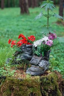 Stivale turistico con fiori nella foresta.