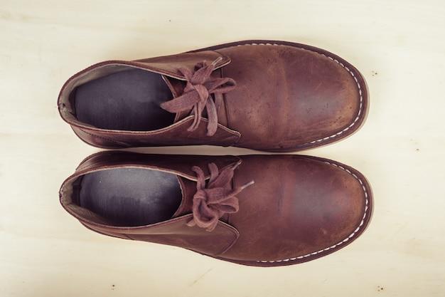 Stivali alla moda marroni su fondo di legno, retro colore