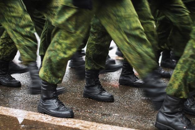 Stivali del soldato che camminano sull'asfalto bagnato durante la sfilata della memoria. i militari marciano per strada. molte scarpe e abbigliamento mimetico. lubrificazione del movimento