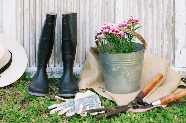 Stivali di gomma con fiori e attrezzi in giardino