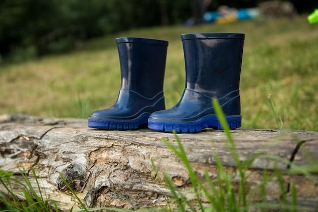 Stivali di gomma per bambini stanno sulla trave, il concetto di campeggio e ricreazione