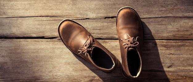 Stivali eleganti marroni su legno