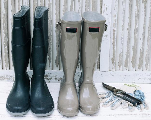 Stivali impermeabili e potatore su legno bianco