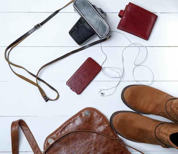 Stivali in pelle marrone, smartphone in una custodia con cuffie, borsa e vecchia macchina fotografica vintage in una custodia nera