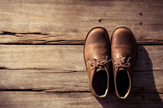 Stivali marroni eleganti su legno