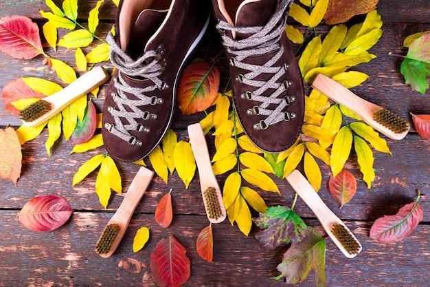 Stivali marroni in camoscio su superficie in legno con foglie,