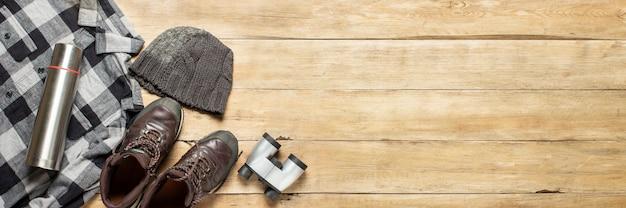 Stivali per una pista, camicia, cappello, binocolo su un fondo di legno. concetto di escursionismo, turismo, campo, montagne, foresta.